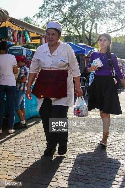 woman wearing cap and apron walking at almaty bazaar - sergio amiti stock pictures, royalty-free photos & images