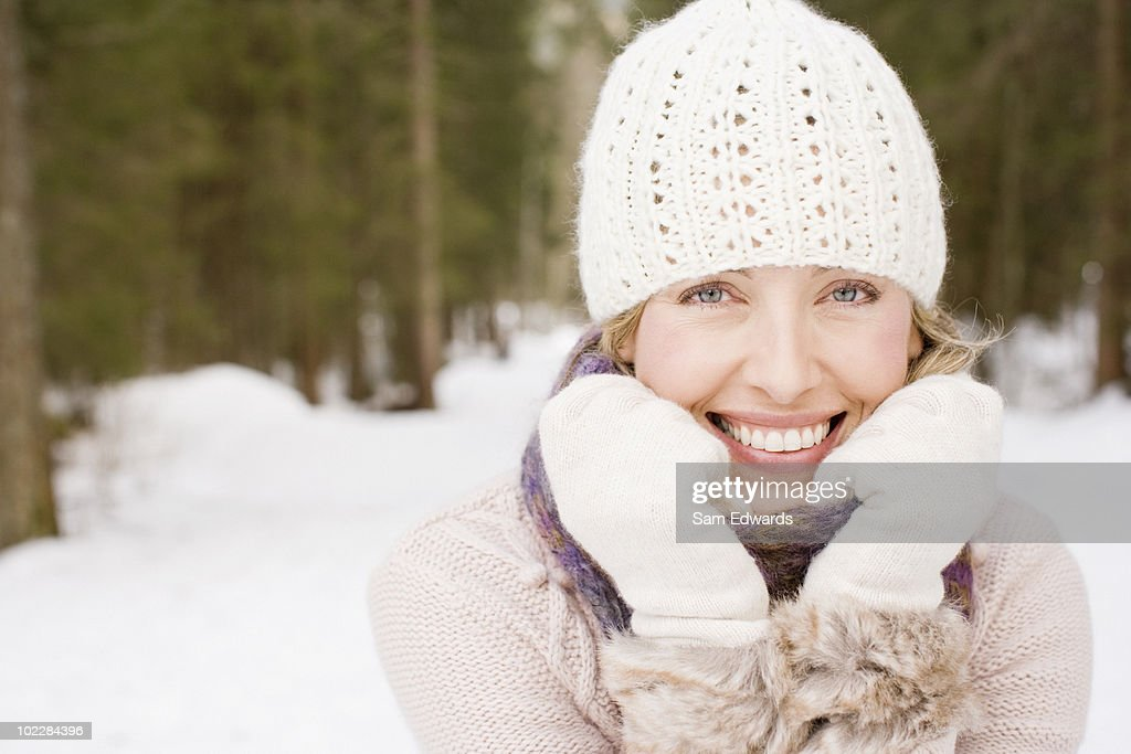Woman wearing cap and gloves in snow : Stock Photo