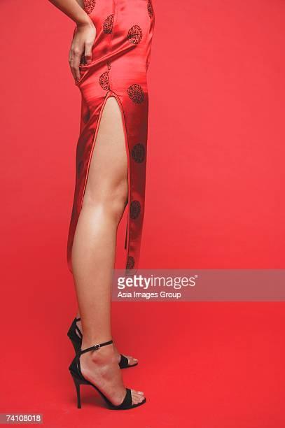 Woman wearing cheongsam and high heels, hands on buttocks