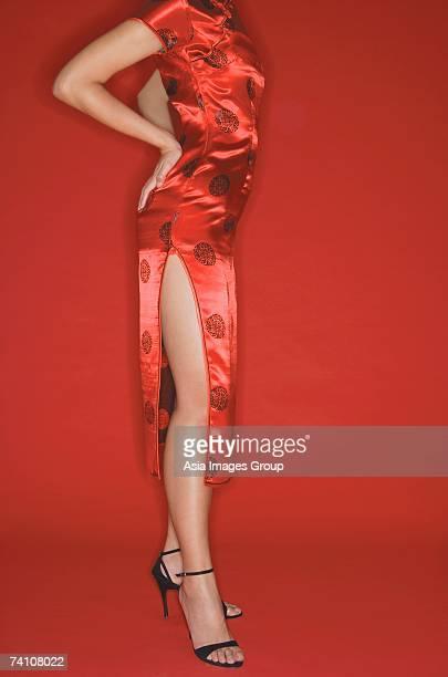 Woman wearing cheongsam and high heels, hands on hips