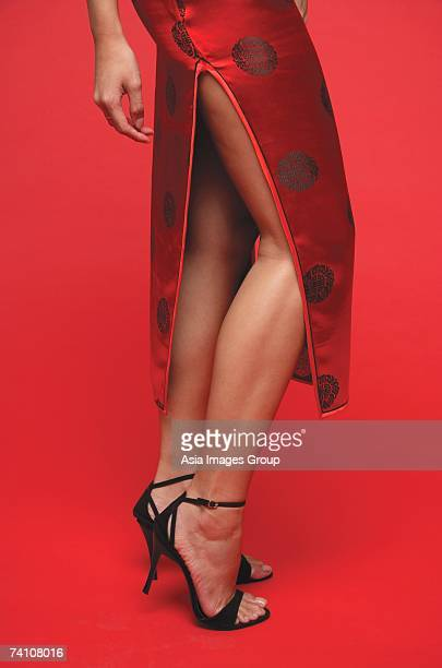 Woman wearing cheongsam and high heels, low section