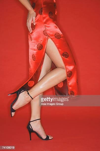 Woman wearing cheongsam and high heels, standing on one leg