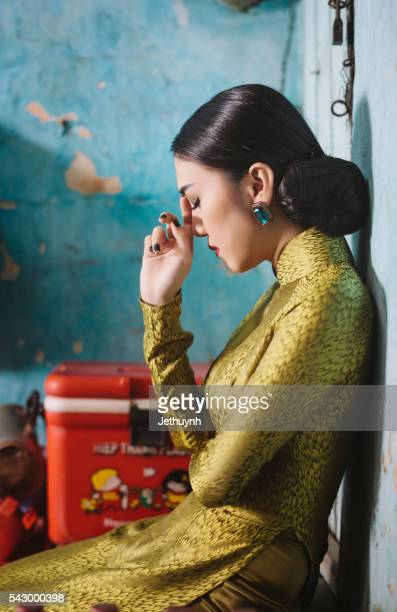 woman wearing classical aodai long dress felling tired - long dress stock pictures, royalty-free photos & images