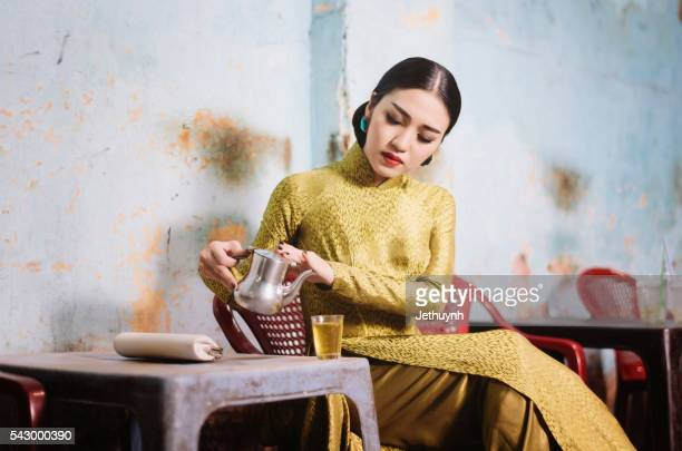 Woman wearing classical Aodai sitting in an ancient coffee shop, China Town, Saigon