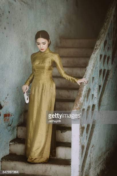 Woman wearing classical Aodai walking at stair in an ancient town, China Town, Saigon
