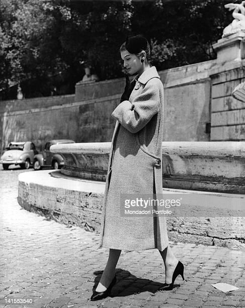 A woman wearing coat cloak hat and gloves by Ferdinandi 1955