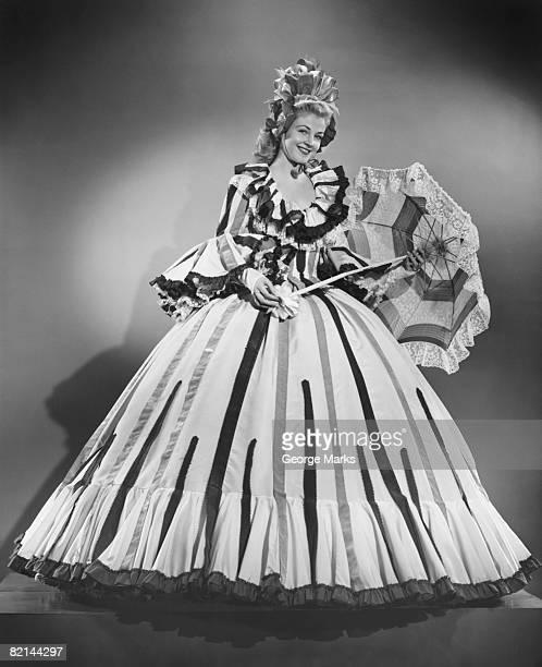 Woman wearing colonial style dress posing in studio, (B&W), portrait
