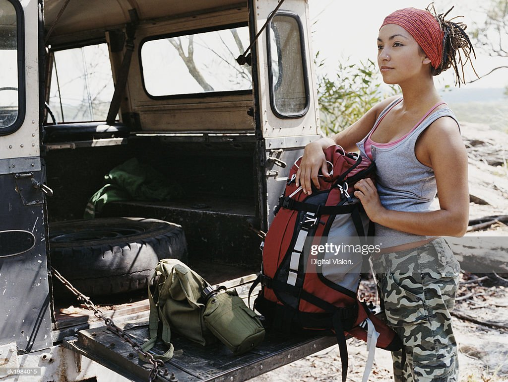 Woman Wearing Combat Trousers Unloading a Jeep : Stock Photo