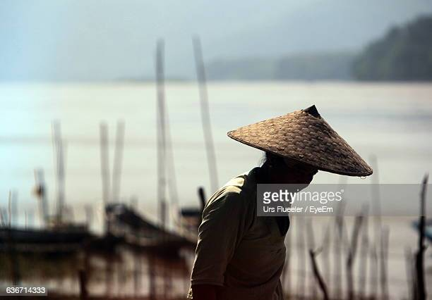 Woman Wearing Conical Hat Against Sea