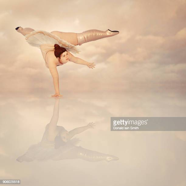 woman wearing corset and boots balancing on hand in clouds - fat woman funny stock photos and pictures