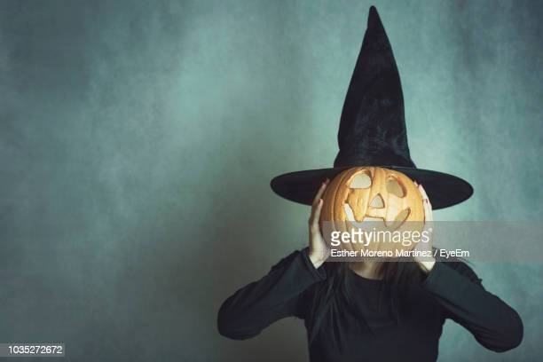 woman wearing costume covering face with jack o lantern against wall during halloween - happy halloween stock photos and pictures