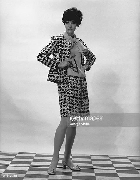 Woman wearing costume posing in studio, (B&W), portrait