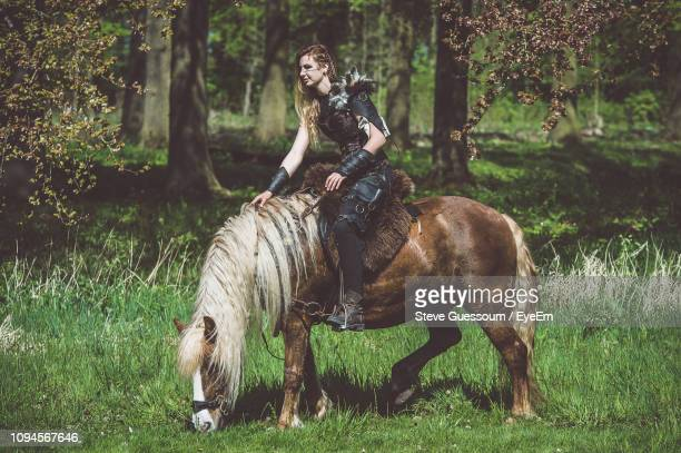 woman wearing costume riding horse on field - steve guessoum stockfoto's en -beelden