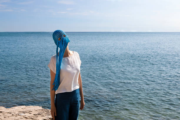 Woman wearing crocheted blue headdress with fringes standing in front of the sea