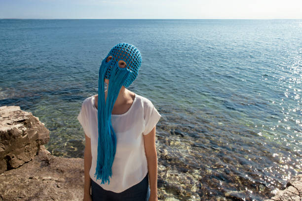 Woman wearing crocheted blue headdress with fringes standing in front of the sea looking up