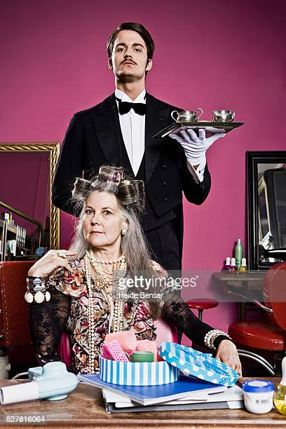 woman wearing curlers, butler in background - butler stock pictures, royalty-free photos & images