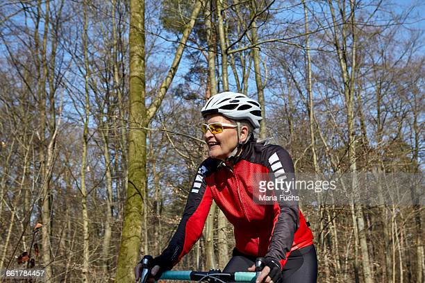 Woman wearing cycling helmet and sunglasses cycling, looking away smiling