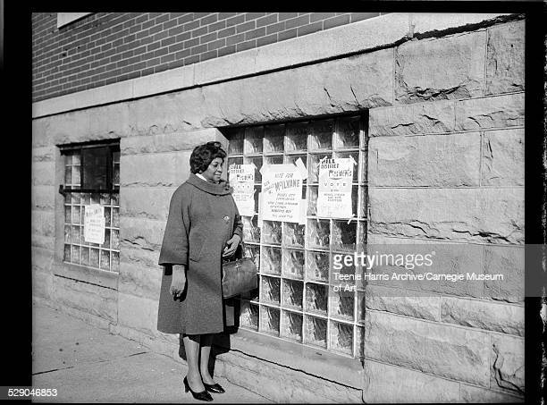 Woman wearing dark jacket with rounded collar standing beside exterior glass block window with signs taped on window reading 'Vote for Rev Donald W...