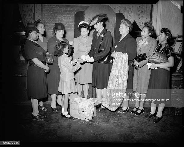 Woman wearing dark suit and hat, handing cup and saucer to little girl wearing Red Cross patch on sleeve of coat, with seven other women standing...