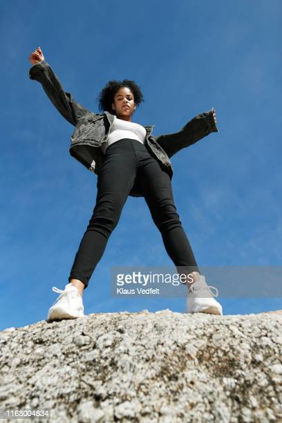 woman wearing denim jacket on rock against blue sky - low angle view - fotografias e filmes do acervo