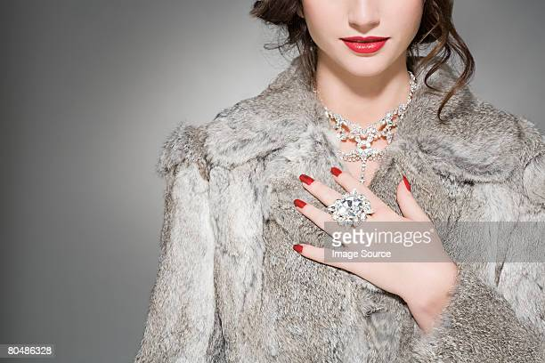 woman wearing diamonds and a fur coat - diamond necklace stock pictures, royalty-free photos & images