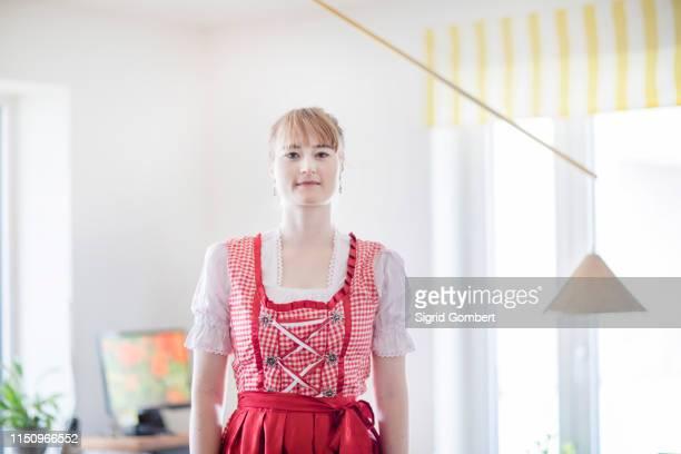 woman wearing dirndl in home office - sigrid gombert - fotografias e filmes do acervo
