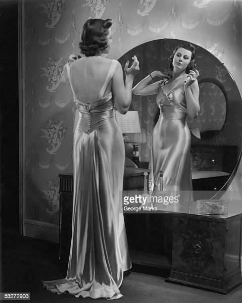 Woman wearing dress looking in mirror