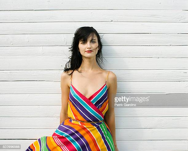 woman wearing dress standing beside house - multi colored dress stock pictures, royalty-free photos & images