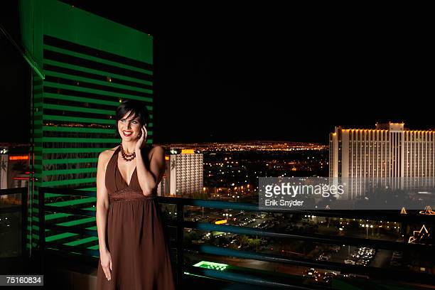 Woman wearing dress standing on balcony smiling, using mobile phone, illuminated cityscape in background
