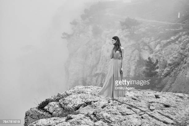 Woman wearing dress standing on rock in fog