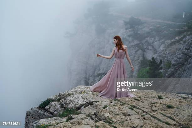 woman wearing dress standing on rock in fog - long dress stock pictures, royalty-free photos & images