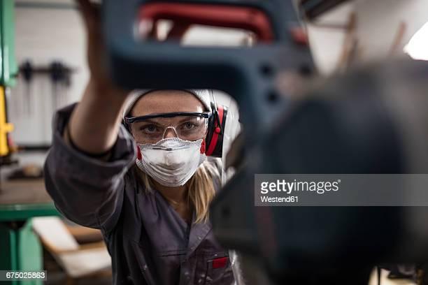 woman wearing earmuffs and dust mask working on machine - schutzbrille stock-fotos und bilder