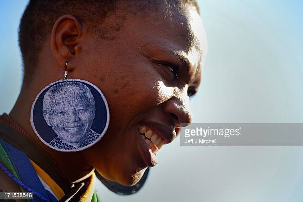 A woman wearing earrings depicting former South African President Nelson Mandela joins other people gathering to leave messages of support for him...