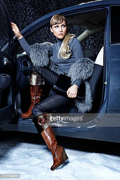 woman wearing elegance boots sitting in car at night time