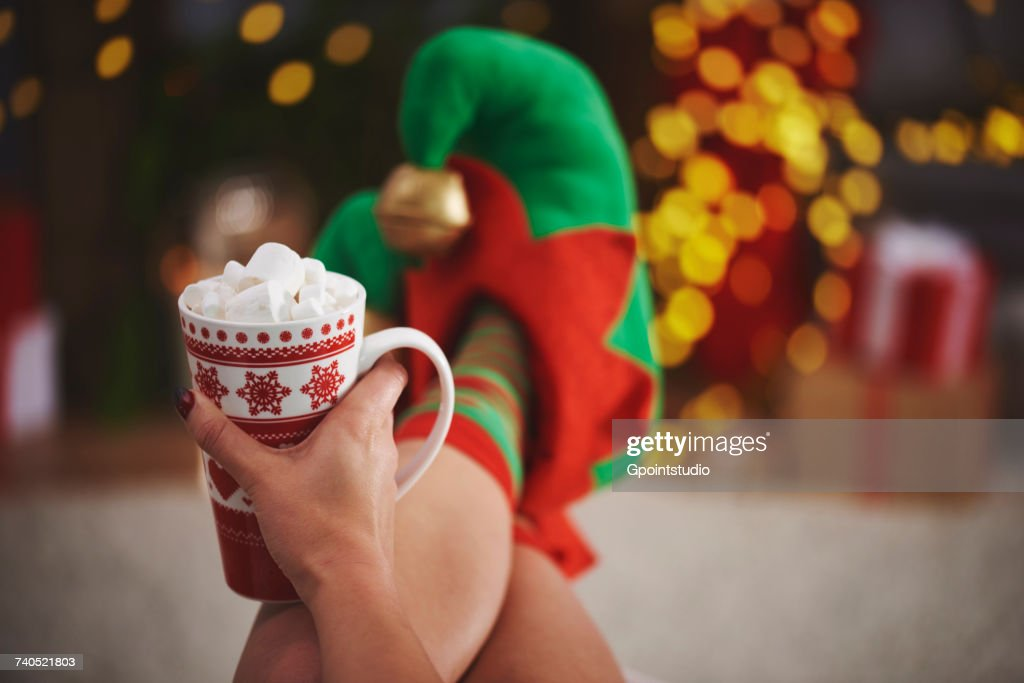 Woman wearing elf slippers holding hot chocolate : Stock Photo
