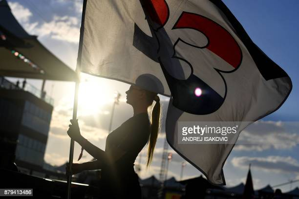 A woman wearing Etihad Airways cabin crew members' outfits holds a flag bearing the number of Red Bull's Dutch driver Max Verstappen ahead of the Abu...