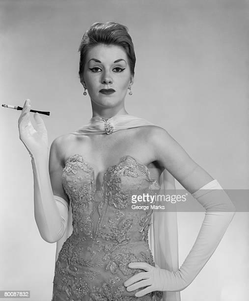Woman wearing evening dress, holding cigarette, portrait