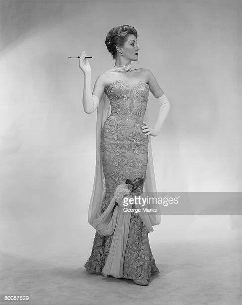 woman wearing evening dress, holding cigarette, studio shot - evening glove stock pictures, royalty-free photos & images