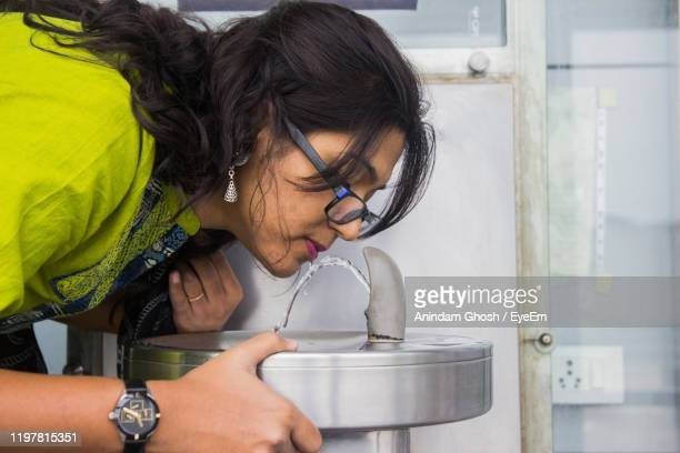 woman wearing eyeglasses drinking water at fountain - fountain stock pictures, royalty-free photos & images