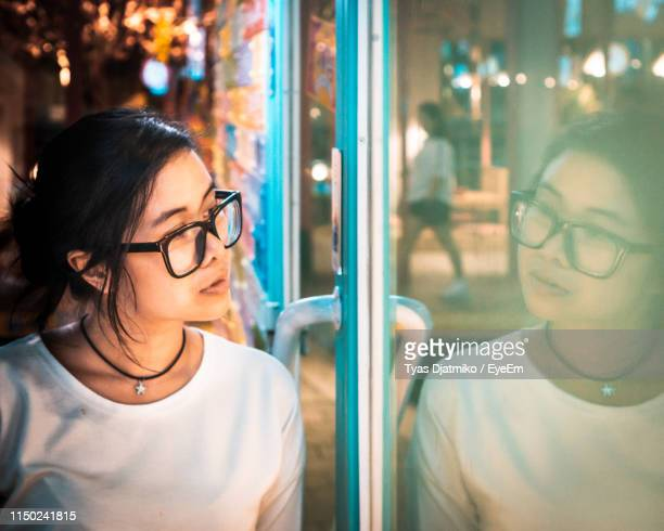 woman wearing eyeglasses looking in window at night - one mid adult woman only stock pictures, royalty-free photos & images