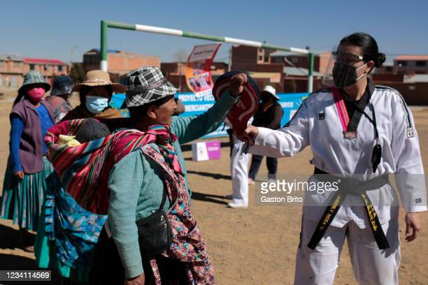 Woman wearing face mask and traditional clothes give a hits a pad held by taekwondo instructor Kimberly Nosa of Warmi Power on July 22, 2021 in El...