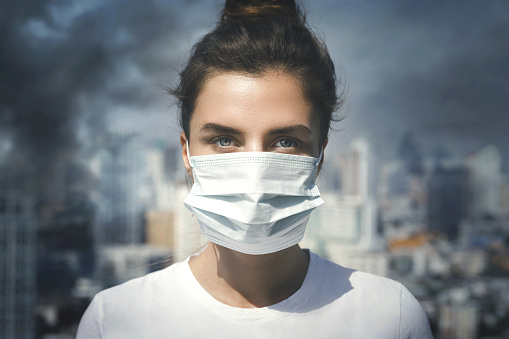 Woman wearing face mask because of air pollution in the city 1016687670