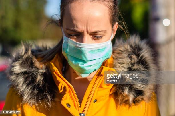 woman wearing face mask because of air pollution in the city. - mask stock pictures, royalty-free photos & images
