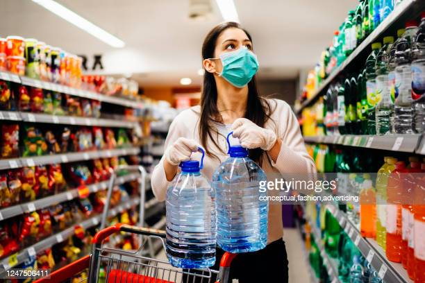 woman wearing face mask buying bottled water in supermarket/drugstore with sold-out supplies.prepper buying bulk supplies due to covid-19 or coronavirus and panic buying concept. - 口を使う ストックフォトと画像