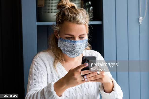 woman wearing face mask sitting alone in a cafe, using mobile phone, working remotely. - holding stock pictures, royalty-free photos & images