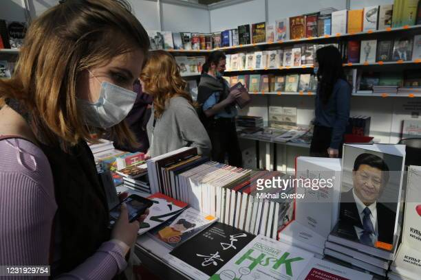 Woman wearing face mask to protect herself against the coronavirus looks on the book by Chinese President Xi Jinping while visiting the Non/fiction22...