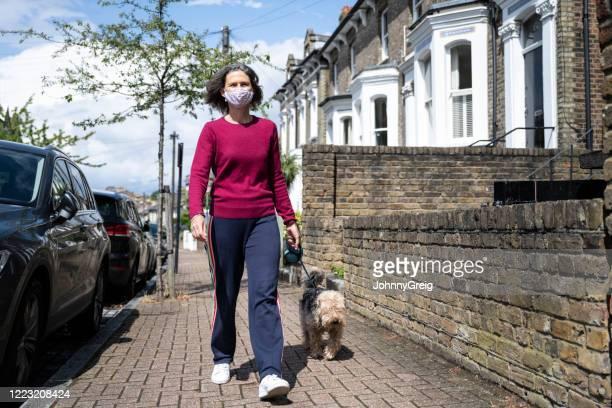 woman wearing face mask walking dog along pavement during coronavirus pandemic - london breed stock pictures, royalty-free photos & images