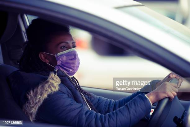 woman wearing face mask while driving a car. - driving mask stock pictures, royalty-free photos & images