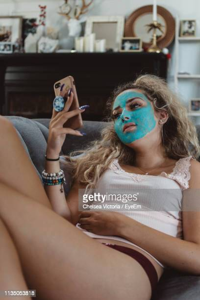 woman wearing face mask while using mobile phone at home - chelsea mask stock pictures, royalty-free photos & images
