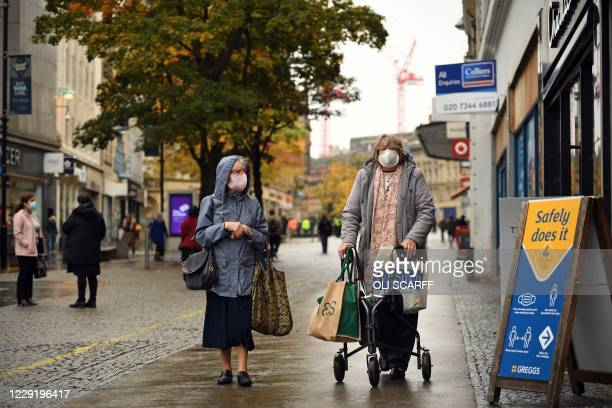 Woman wearing face masks or covering due to the COVID-19 pandemic, walks along the pavement in the shopping district in central Sheffield, south...